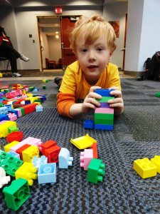 Kevin builds with Duplo blocks during a Kids @ Work session at Mentor Library.