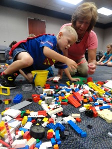 Tyler picks the blocks he needs from the pile. (And, yes, he's wearing a Superman shirt and cape. No, that's not pertinent, but it IS awesome..)