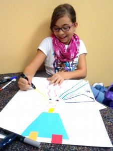 Giselle laughs as she draws brightly colored shocks of hair during the Studio MPL meeting Monday.