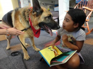 Diva, one of our therapy dogs from Paws to Read, interrupts Leah's reading for a canine kiss.