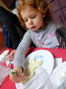 Emily traces the outline of her cookie man with frosting during a holiday story time on Saturday at Mentor Public Library.