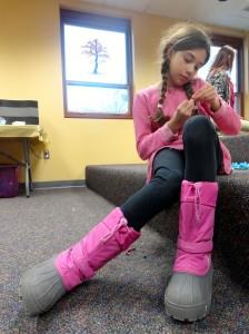Abby threads her yarn through her dreamcatcher.