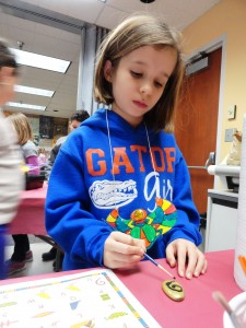 Rose paints her amulet during the Studio MPL meeting at Mentor Library.