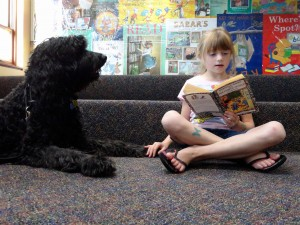Claire touches Kody's paw as she reads to him about Horrible Harry.
