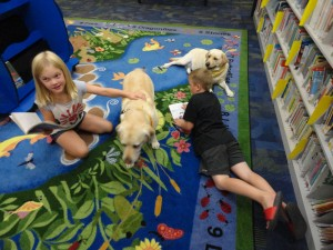 That's a pile of pups! Ava and Jake read to Hannah and Honey.