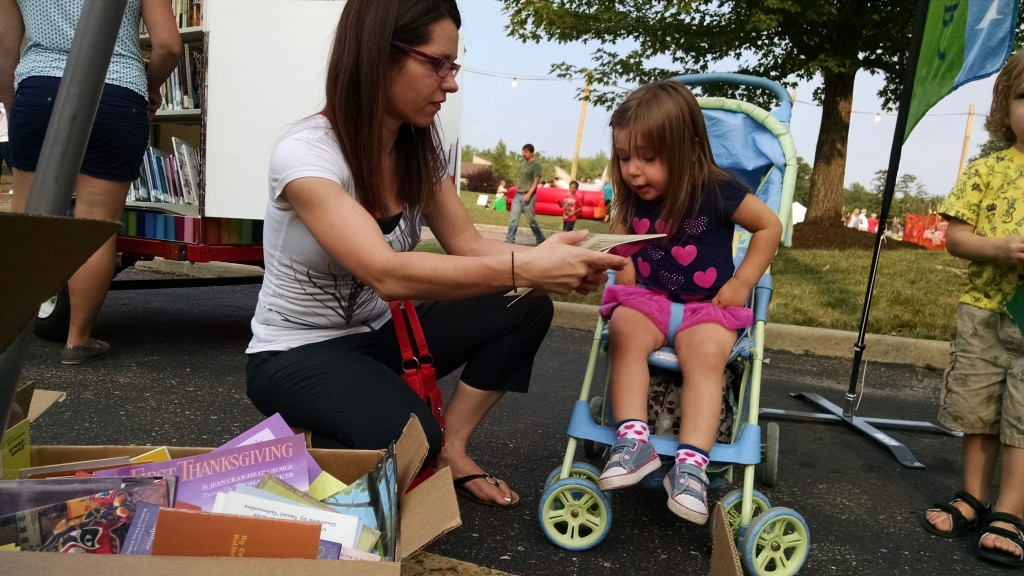 Violet's mom helps her pick a book from our Pop-Up Library.