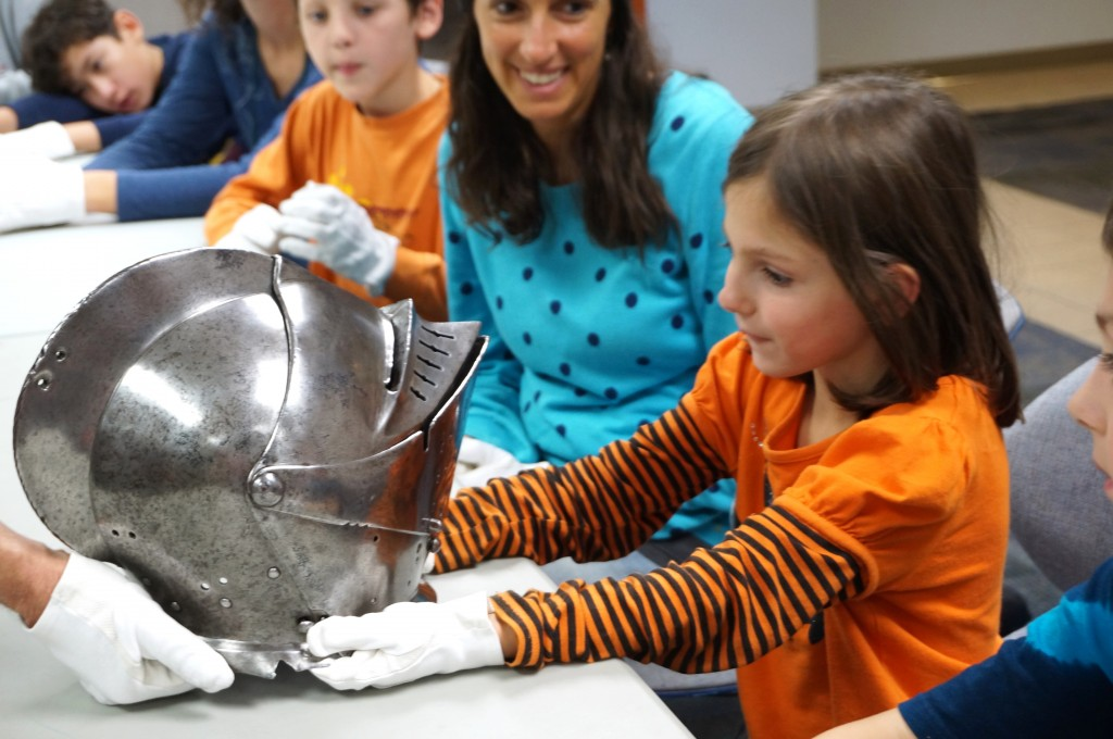 Alyssa takes a close look at a helmet that is hundreds of years old.