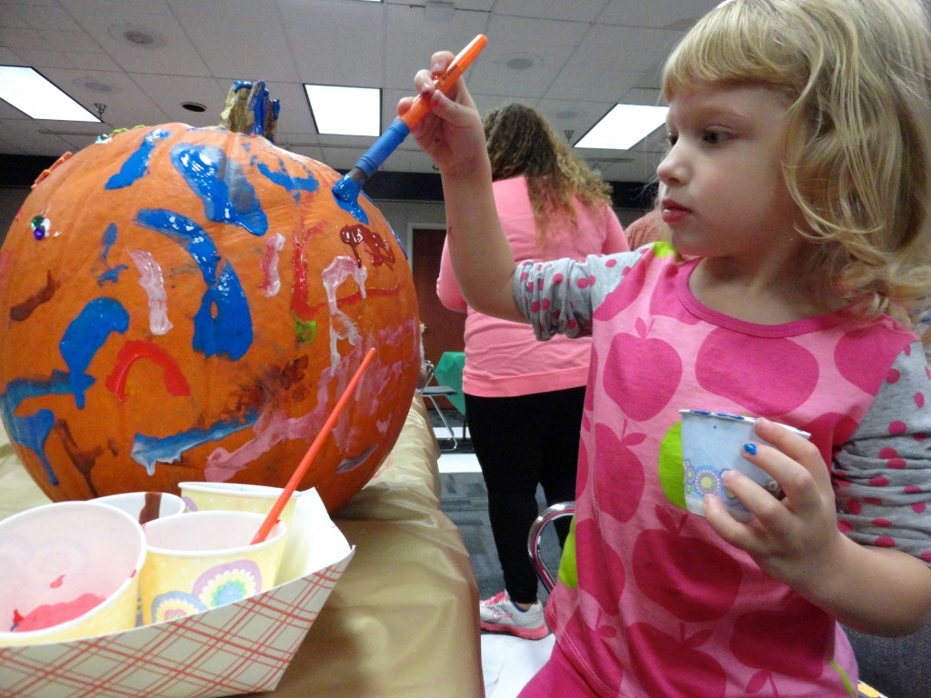 Peyton gives her pumpkin the Jackson Pollock treatment during our Pumpkin Decorating program at Mentor Library.