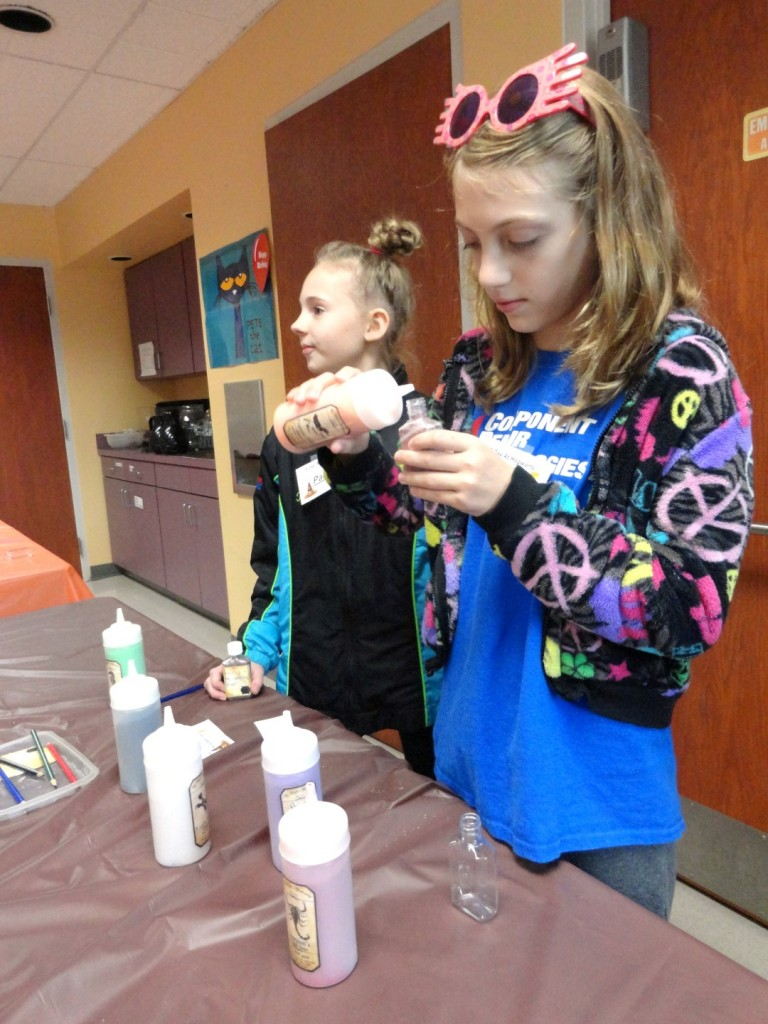 Jaden makes sand art, mixing the various colors during the potions class.