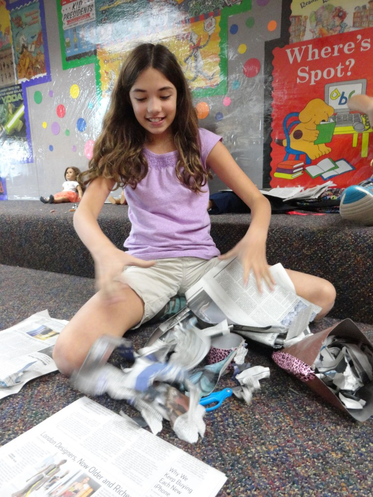 Abby tears newspaper to stuff her sit-upon.