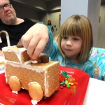 Caleigh carefully places peanut butter cups onto her graham cracker train.