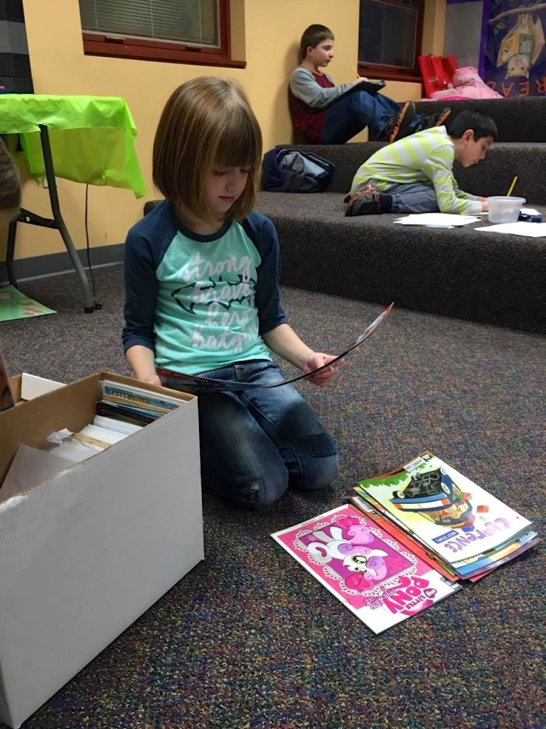 Claire browses through issues at Mentor Public Library's Comics Club