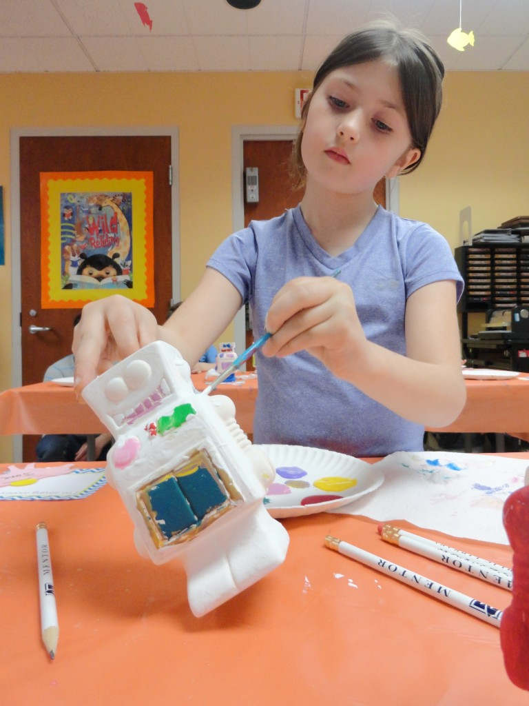 Jovie tilts her robot's neck so she can paint it more easily.