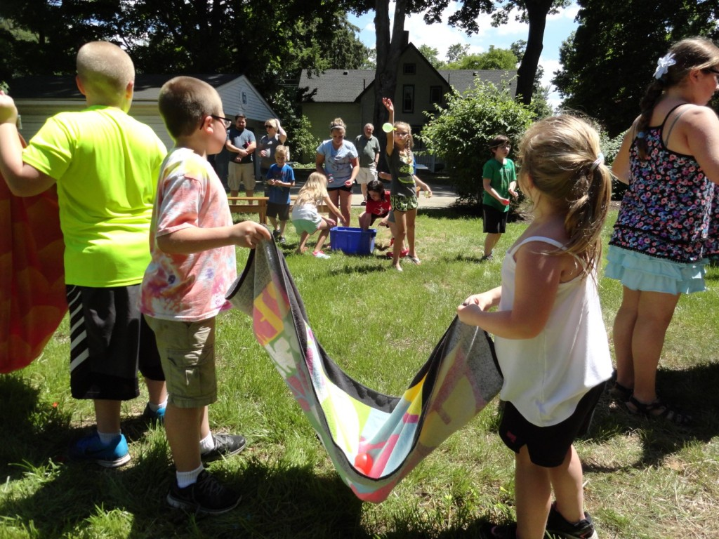 The teams had to work cooperatively to catch water balloons in a beach towel.