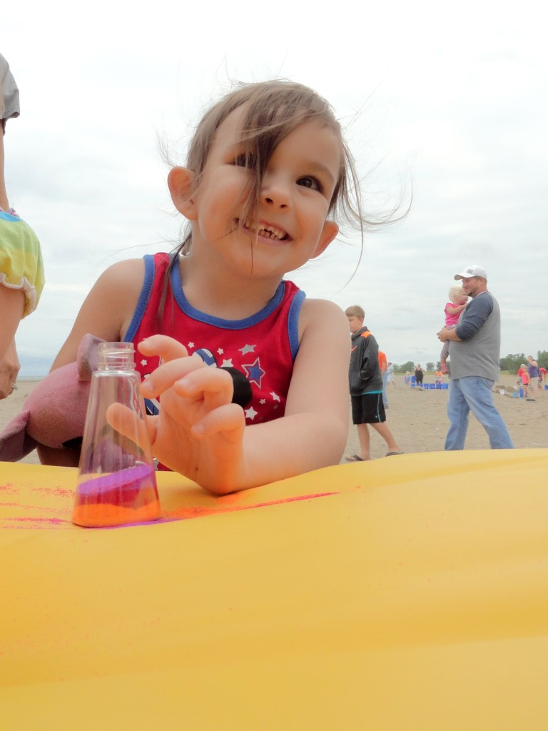 Estella uses colorful sand to make art during BeachFest.