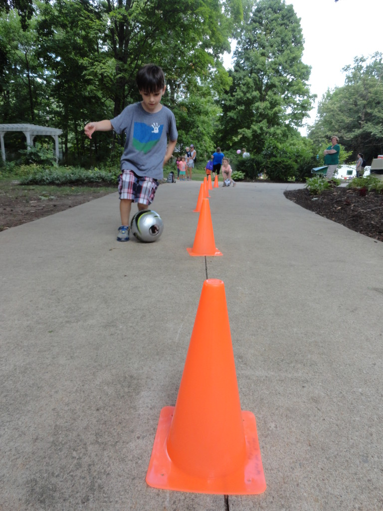 Eli weaves between the cones with his soccer ball.