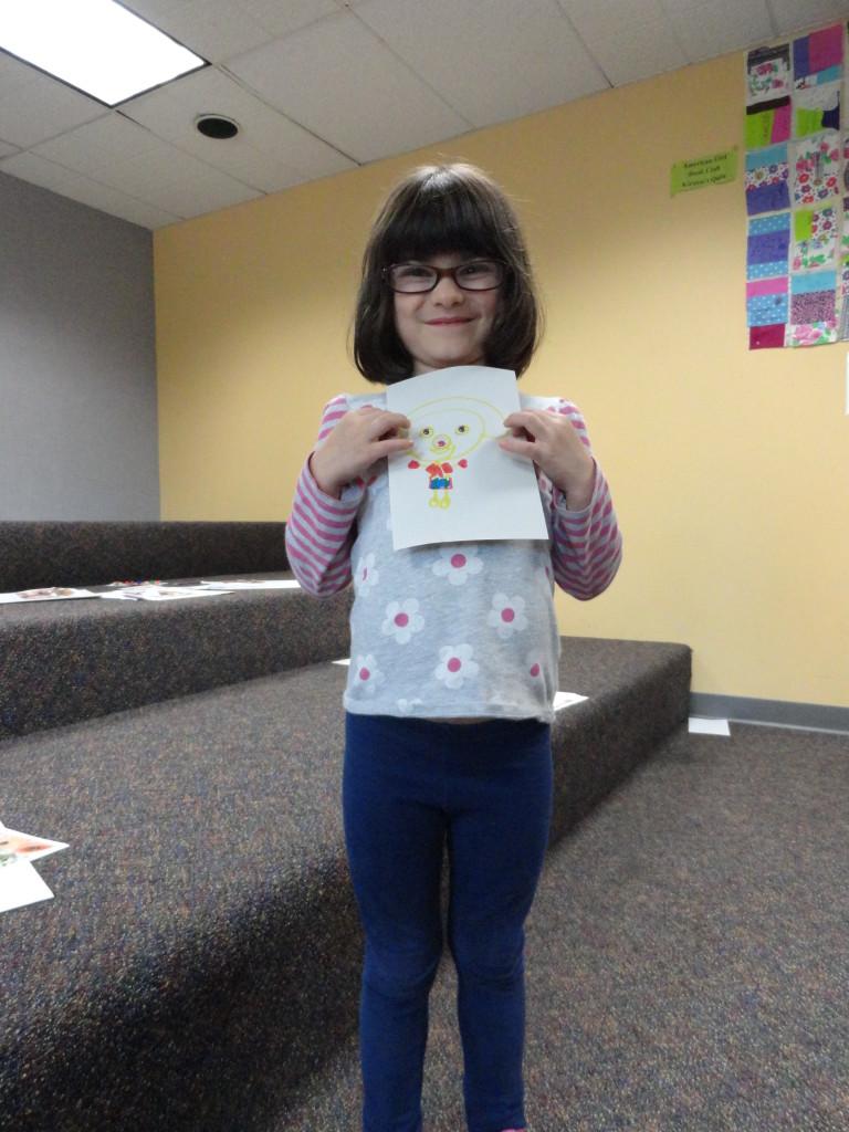 Isabella shows off her finished artwork.
