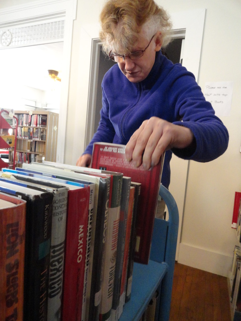 Sharon Link, another volunteer from Deepwood's Willoughby Branch, helps shelve the books  in MPL's Read House.
