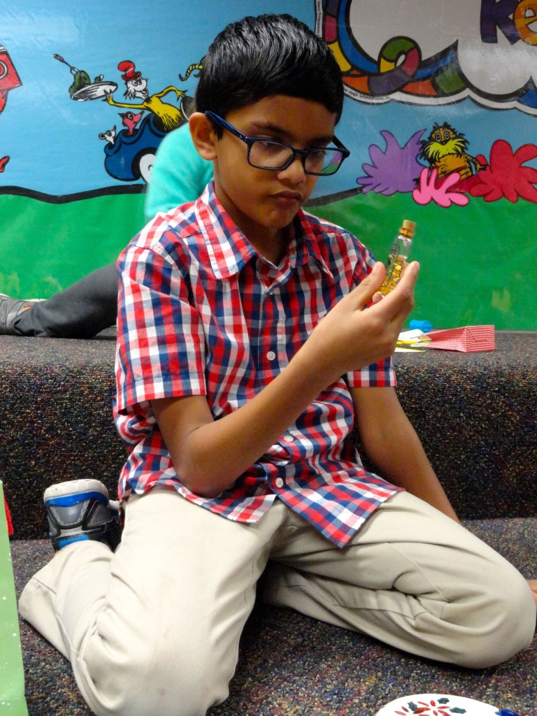 "Santosh Akilesh inspects the contents of his holiday ""gift bag."" He had to compose a story using the items in his bag."