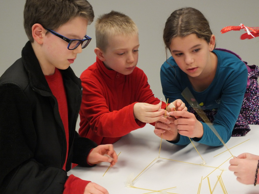 Alex, Caleb, and Sabine work together to build a stable tower using spaghetti noodles.
