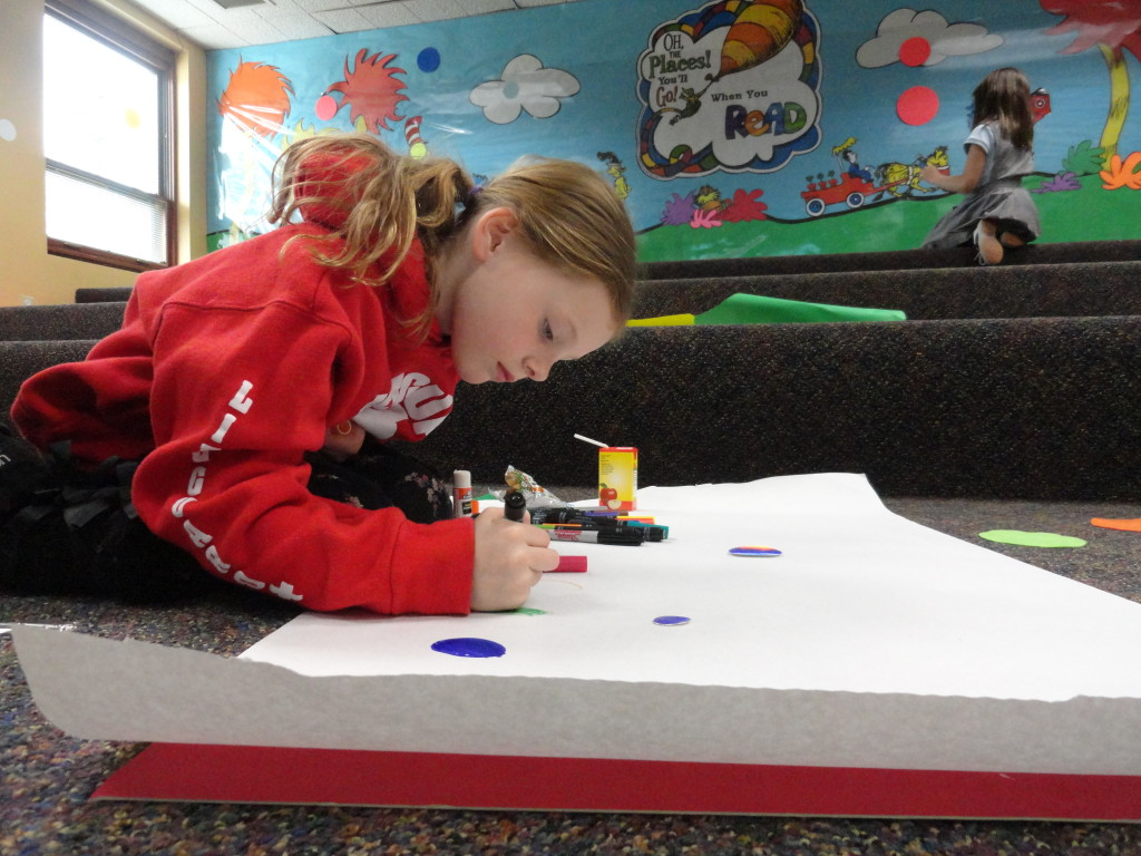Maggie adds polka dots of different size and color to her canvas.