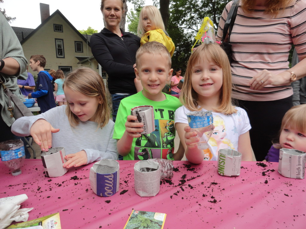 Young green thumbs plant tomato, spinach and kale seeds in their newspaper planters.