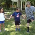 Josh passes a hula-hoop to Jude. They had to pass the hoop around an entire circle without anyone letting go.