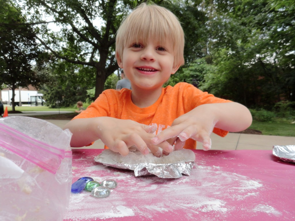 Luca smiles while building his sand sculpture during Make-It Monday.
