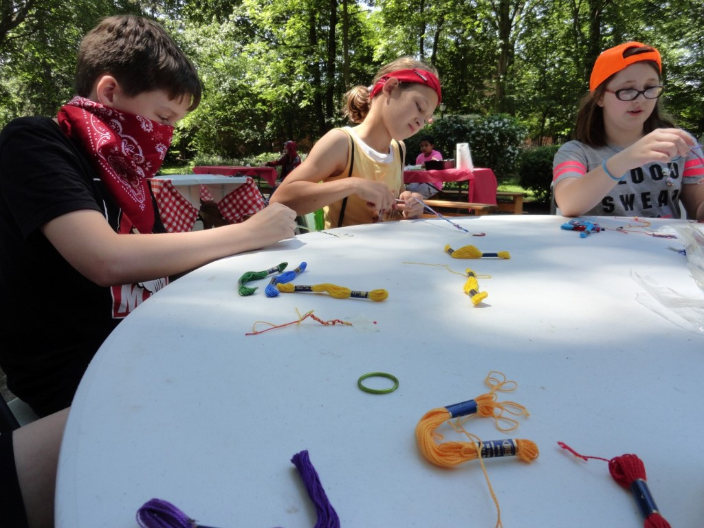 "Lilly decorates her sash with paint. Campers further festooned their sashes by earning pins at ""camp."""