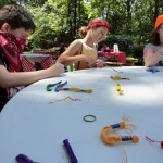 """Lilly decorates her sash with paint. Campers further festooned their sashes by earning pins at """"camp."""""""