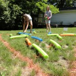 Abby and Lynn play a supersized version of the triangle peg game using pool noodles.