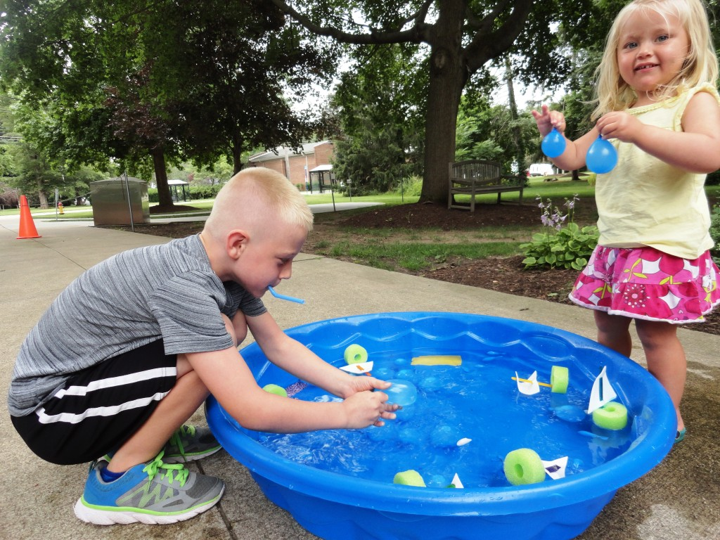 Caleb navigates his boat with a straw while Emmalynn plays with a pair of icebergs that look suspiciously like water balloons.