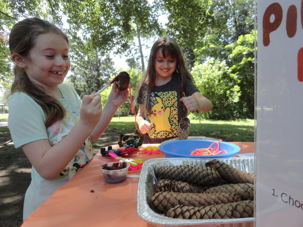 Maggie and Olivia make pinecone birdfeeders during Make-It Monday at our Read House.