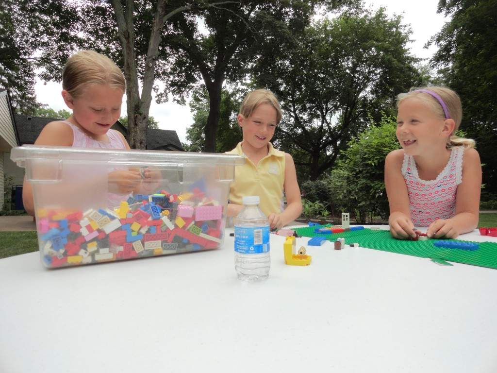 The girls debate layout while building a house with LEGO bricks during Make-It Monday.