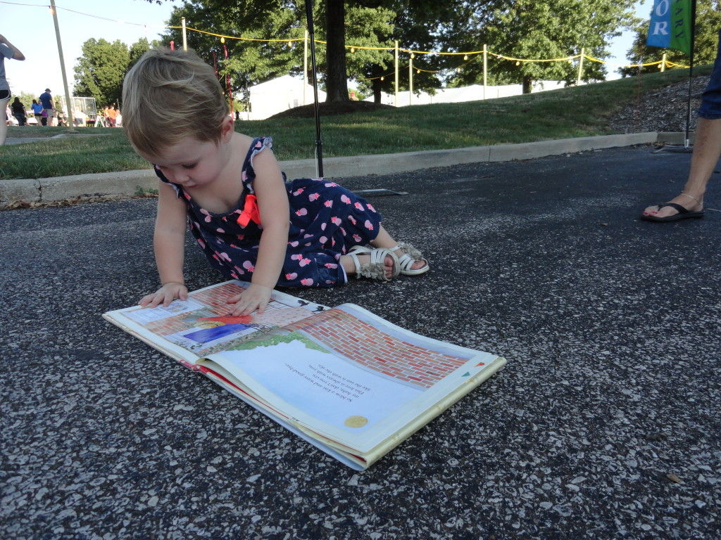 A young reader finds her new favorite book on our Pop-Up Library during CityFest.