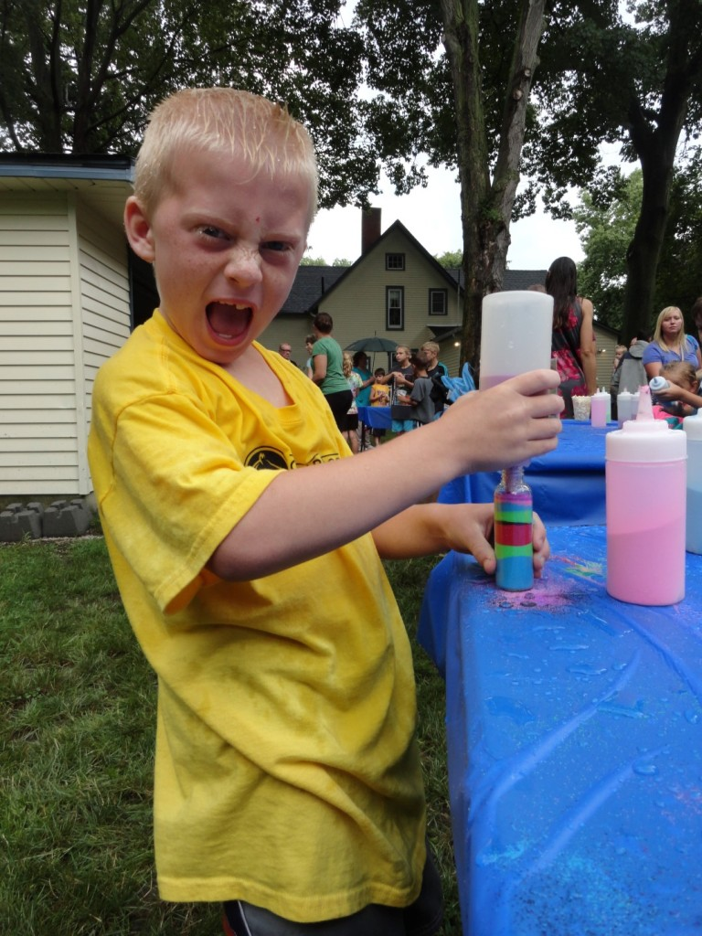Sebastian makes sand art during Mentor Public Library's Summer Reading Finale Party.