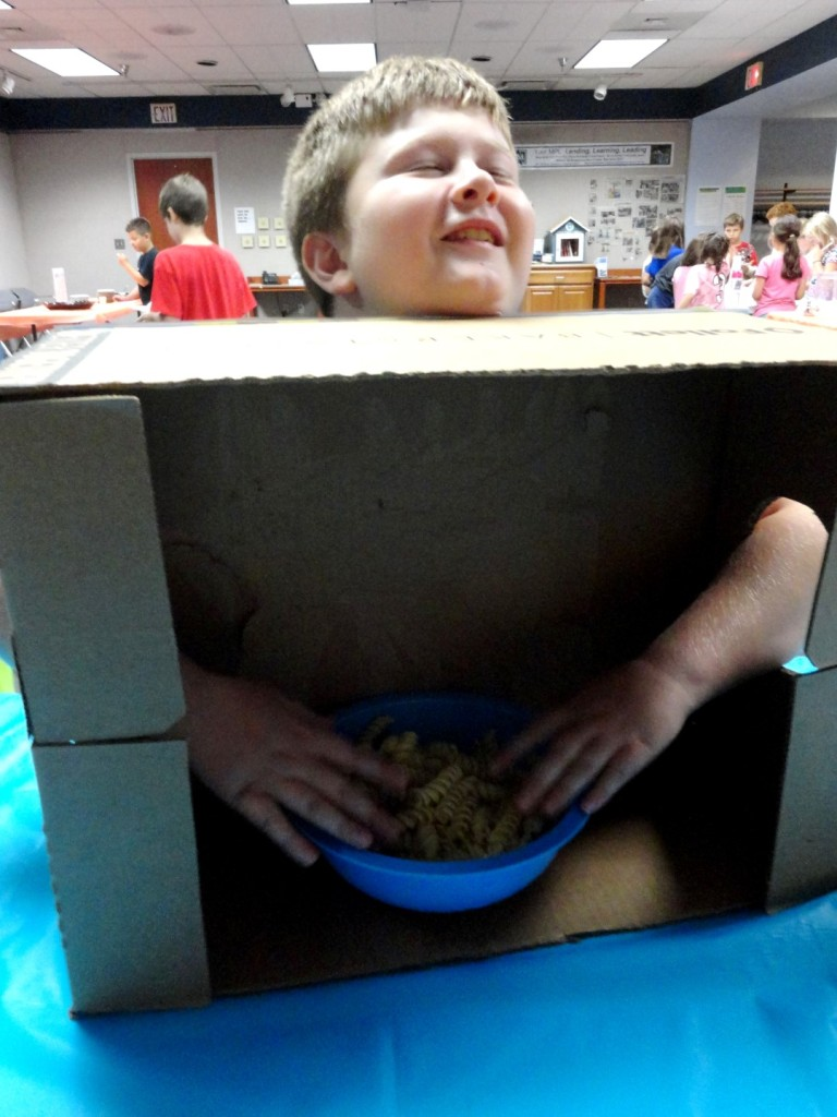 Austin tries to figure out what is in one of our mystery boxes during the senses program at Mentor Public Library.