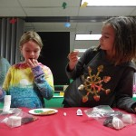 Madelyn nibbles her supplies while making a marshmallow snowman.