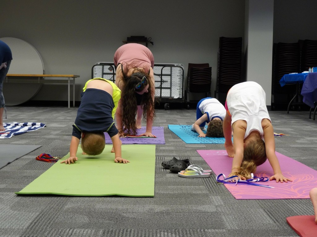 The kids introduce themselves using yoga poses, including down dog, during Yoga Story Time.