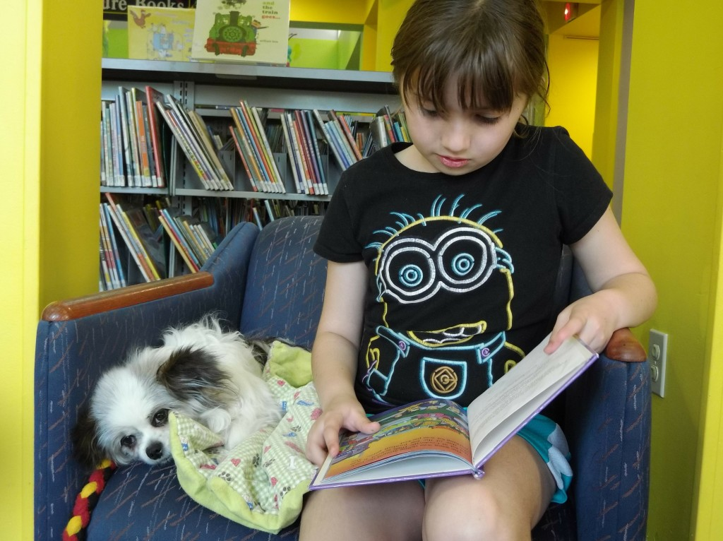 Maddie and Caesar share a book during Paws to Read.