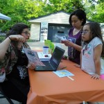 Ms. Amy helps families sign up for Summer Reading.
