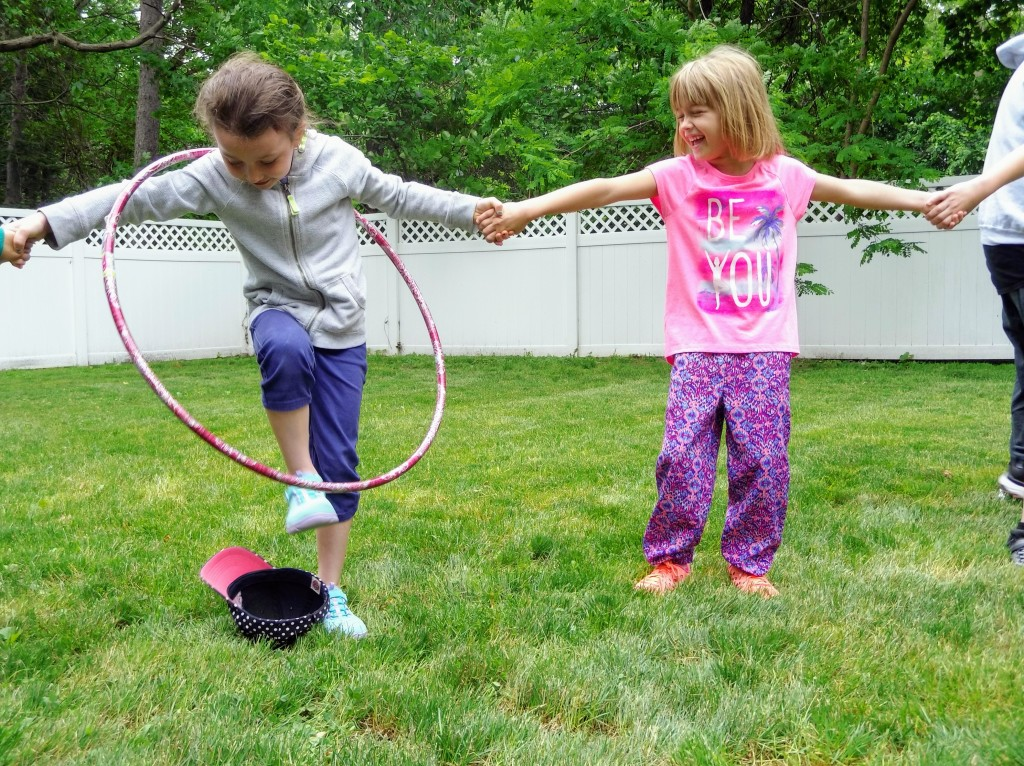 Kids try to pass a hula hoop from person to person without unclasping hands.