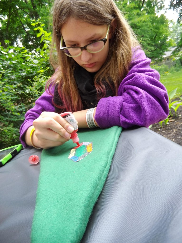 Lily uses puff paint to draw a rupee onto her kokiri cap during our Ocarina of Summertime program.