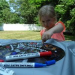 Kylie carefully places gem stones around her decorated record.