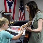 Vincent strums the guitar while Ms. Annie sings