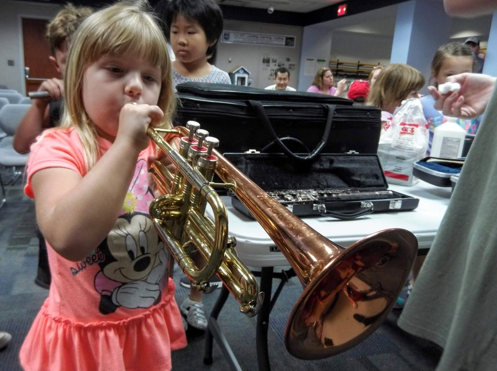 Elana learns how to buzz into a trumpet.