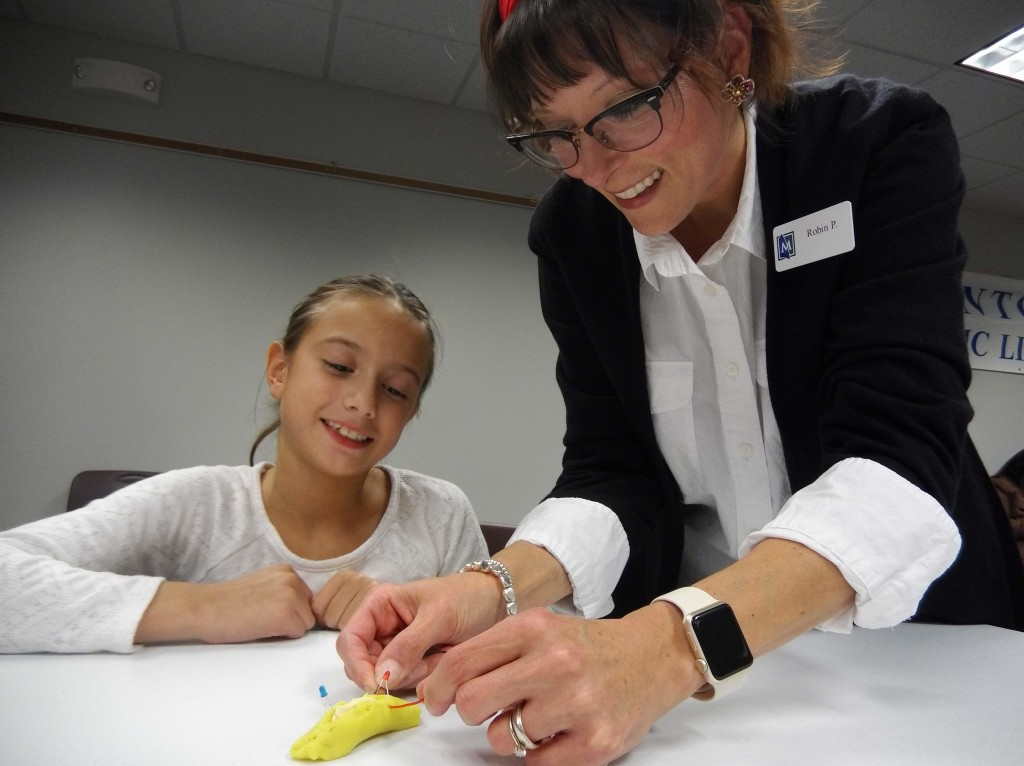 Ms. Robin helps Sarah make a circuit with play-dough, clay and two light-emitting diodes.