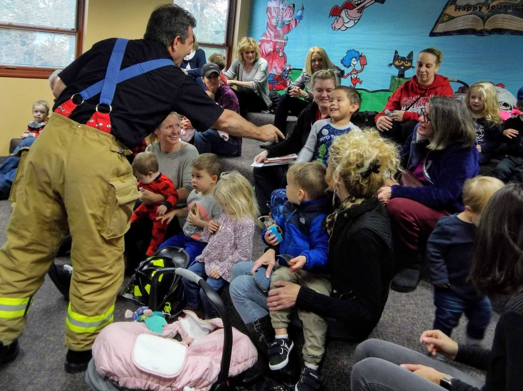Firefighter Jerry shares stickers with the kids at story time.