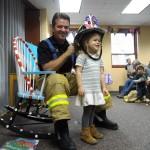 Gigi tries on Firefighter Jerry's helmet.