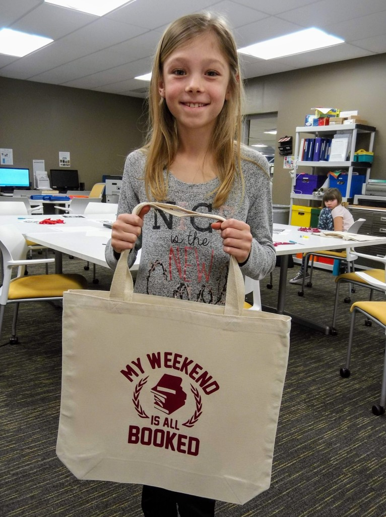Gwen shows the custom tote bag she made at The HUB's makerspace.